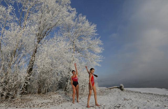 """Cô bé Nastya Usachyova, 9 tuổi, một trong những thành viên nhí của câu lạc bộ, cùng mẹ làm ấm cơ thể, trước khi xuống dòng sông Yenisei. """"Ban đầu, cháu cũng thấy lạnh lắm, nhưng rồi cũng vượt qua được"""", cô bé nói."""