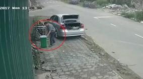 Người đàn ông đi ô tô trộm thùng rác bên đường