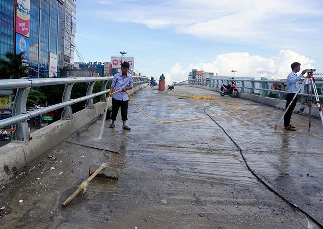 Các kỹ sư hỗ trợ công nhân dọn dẹp, phun nước lau chùi trên cầu vượt.