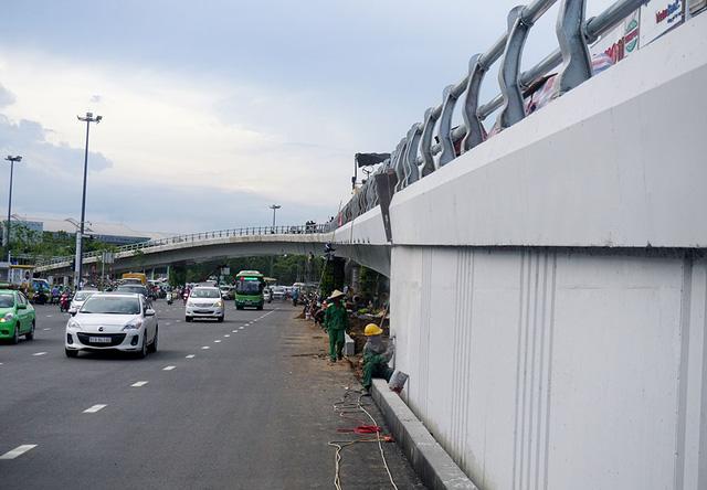 Dự kiến, công trình sẽ thông xe và khánh thành ngày 3/7. Các công nhân đang tẩy những vết bẩn bám trên thành cầu.