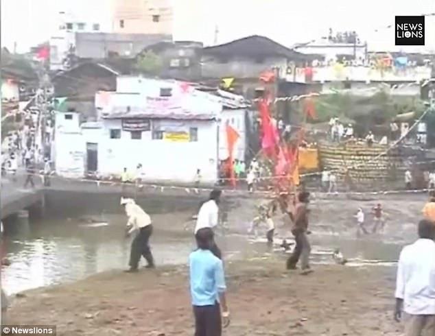 Người dân tụ tập hai bên bờ sông và ném đá về phía những người đang tranh cướp cờ phía dưới