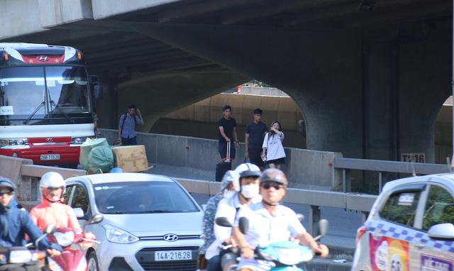 Một số hành khách tự đi bộ từ đường trên cao xuống, len lỏi qua hàng loạt ô tô đang lưu thông.