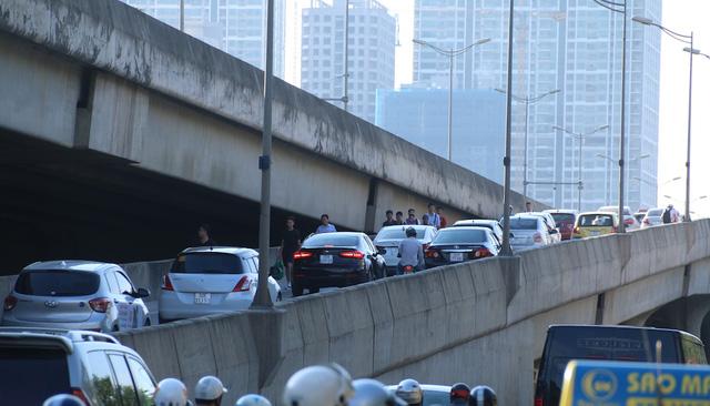 Hành khách đi bộ xuống nút chuyển làn lên cao tốc trên cao hướng từ Khuất Duy Tiến đi Mỹ Đình, trong khi có rất đông phương tiện ô tô đang lưu thông từ dưới lên.