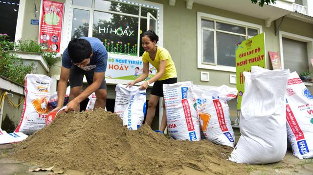 """Lo sợ ảnh hưởng của hoàn lưu bão số 10 có thể gây mưa lớn, ngập lụt nhiều người dân tại khu đô thị Nam An Khánh (Hoài Đức, Hà Nội) đã mua cát về, đóng thành bao tải """"đắp đê"""", chắn sóng trước cửa nhà."""