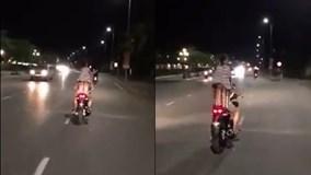 Bố lái xe máy chở con gái đứng trên yên phía sau vô tư nhún nhảy