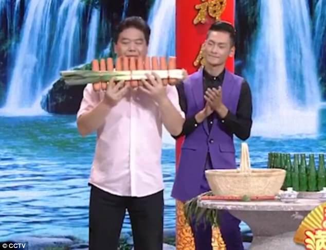 Người đàn ông 48 tuổi đã tự học cách chế tạo và chơi nhạc cụ làm từ rau củ. Trong ảnh, anh Nan đang thổi sáo từ món nhạc cụ làm từ các củ cà rốt và tỏi tây.