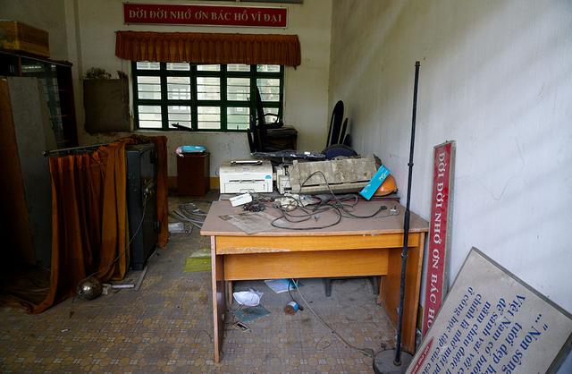 Một căn phòng còn đầy đủ vật dụng nhưng đã nằm chỏng chơ đầy bụi.