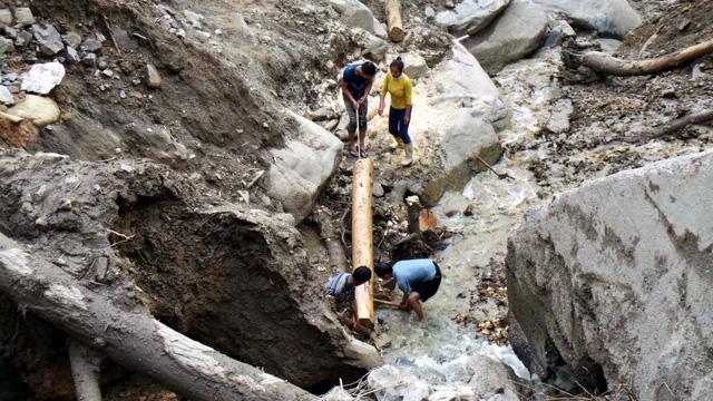 Một số người tranh thủ lấy những khúc gỗ lớn trôi theo đất đá.