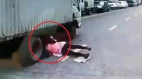 Cô gái ngã vào gầm xe tải, may mắn thoát chết trong gang tấc