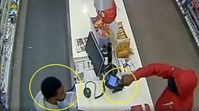 Bị nhân viên nhìn chằm chằm, tên cướp tẽn tò thu súng về, cầm kẹo bỏ đi