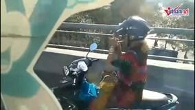 Nữ 'ninja' lái xe máy buông 2 tay, châm thuốc lá trên cầu