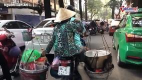Người phụ nữ vô tư chở nồi nước đang sôi đi trên phố Sài Gòn