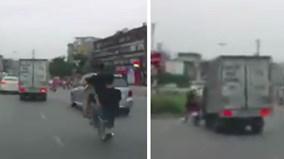 Hai quái xế bốc đầu xe máy, bị ôtô tải quệt văng vào dải phân cách