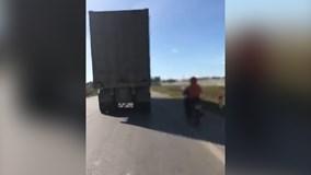 Hoảng hồn 'ninja' xe máy núp hông container để tránh nắng