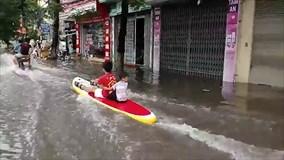 Hai em bé ngồi thuyền lướt sóng trên đường phố đông gây tranh cãi