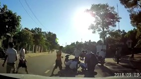 Mặc áo chống nắng quá dài, bé gái bị cuốn vào bánh xe máy của bố