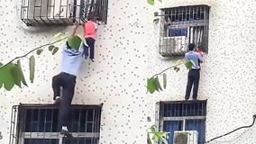 Người đàn ông giải cứu bé trai lọt qua khung sắt lơ lửng giữa không trung