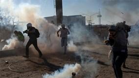 Mỹ nã đạn cao su và phun hơi cay chặn người nhập cư vượt tường rào