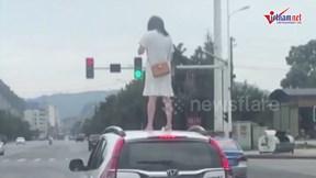 Cãi nhau với chồng, cô gái leo lên nóc xe ô tô giậm chân giận dữ