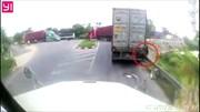 Bị xe container ép sát, cô gái bám vào rào chắn thoát chết