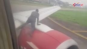 Người đàn ông trèo lên cánh máy bay khi đang chuẩn bị cất cánh