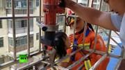 Xem lính cứu hỏa giải cứu bé gái bị kẹt đầu treo lơ lửng giữa tầng 4