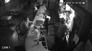 Người đàn ông bình tĩnh ngồi hút thuốc dù bị tên cướp dí súng vào người