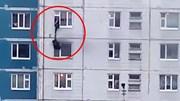Người đàn ông lạ vươn mình ra ngoài cửa sổ cứu cô gái khỏi căn hộ đang cháy