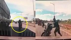 Thanh niên đèo bạn gái núp bóng xe tải tránh nắng còn khiêu khích xe khác