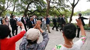 Thủ tướng Nhật Bản Suga Yoshihide đi bộ, vẫy tay chào người dân Hà Nội
