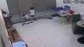 Hãi hùng khoảnh khắc em bé bị cửa cuốn đè ngang người